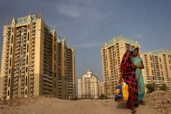 Women walk past high-rise apartments in DLF Ltd. City in Gur