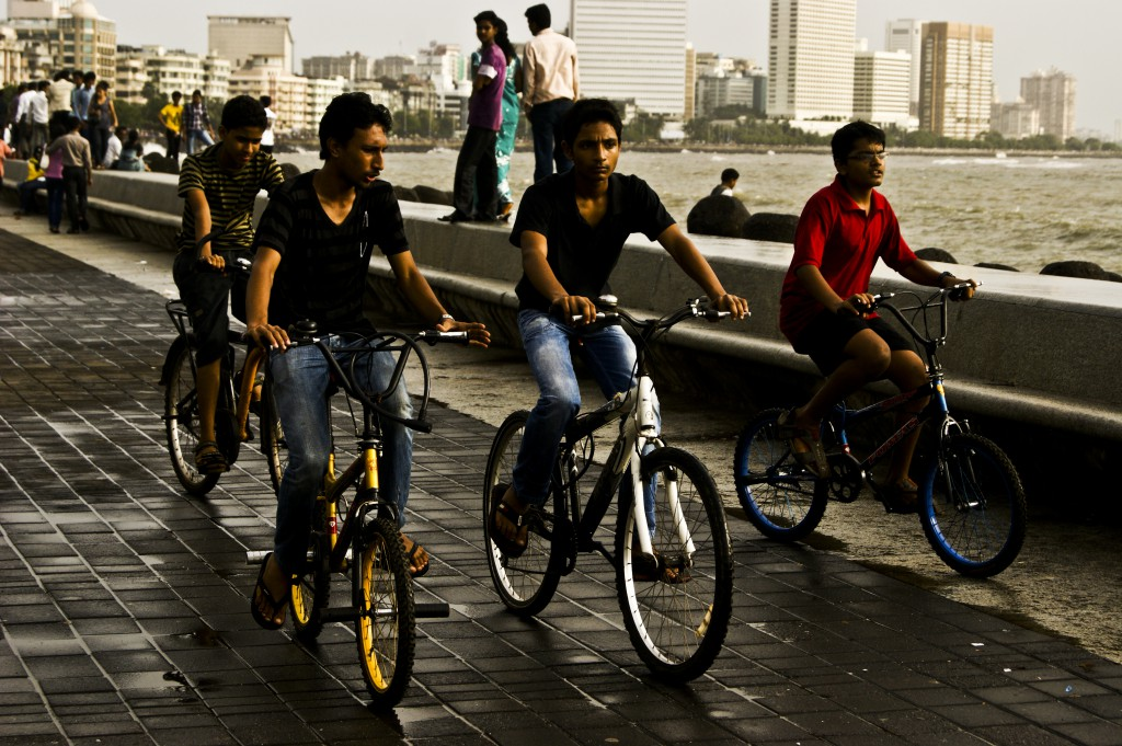 Kids out on their bikes, enjoying the weather, by the Marine Drive which over looks the Arabian Sea